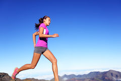 Running sports fitness runner woman jogging. Female athlete training outdoor under blue sky in amazing nature. Multiracial Asian Caucasian female fitness model stock image