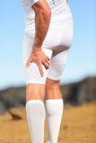 Running sports injury. Pulled hamstring muscle, muscle strain or muscle cramp in back thigh leg of man running outdoors Stock Photos
