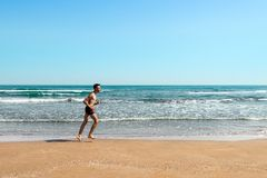 Running sportsman on the beach royalty free stock image