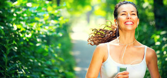 Running sporty girl. Beauty young woman jogging in the park. Running sporty girl. Beauty young woman with earphones jogging in the park stock image