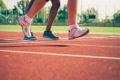 Running legs of white and black sportsmen Stock Photos