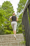 Running on stairs. Sporty woman running on stairs in park stock images