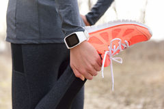 Running stretching - runner wearing smartwatch Stock Images