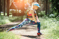 Running stretching. Woman stretching leg as warm-up before run w Royalty Free Stock Image