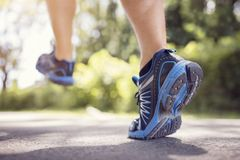 Feet of runner running or jogging on a road in summer Royalty Free Stock Photo
