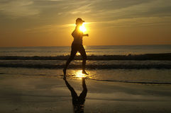 Running Sunset. A woman running barefoot on the beach during sunset / sunrise Stock Images