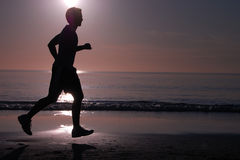 Running at Sunset. Silhouette of a young man jogging on the beach at sunset Stock Photos