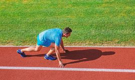 Running tips for beginners. Man athlete stand low start position stadium path. Runner ready to go. Joint mobility. Exercises to improve flexibility and function royalty free stock photos