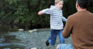 Running to give Dad a hug. Little boy is running along the waterfront into his father`s arms for a big cuddle stock video footage