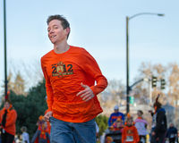 Running to have fun. OISE, IDAHO - NOVEMBER 22, 2012: Young man running to the finish during the Boise Turkey Day 5k charity run stock photos