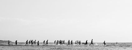 Running to the sea. Monochrome panoramic seascape; Crowd of people racing each other, running to the sea Stock Photography