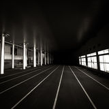 Running to the unknown. The lines of an indoor running track merge into the infinite darkness Stock Photography