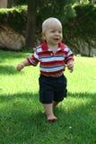 Running Toddler on Grass Stock Image