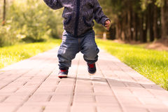 Running toddler in the park at the spring, summer or autumn day.  Royalty Free Stock Photos