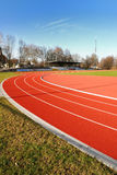 Running track. The image shows a small sports stadium with with a red tartan running track. You see the curve of the track. The picture was taken on a sunny day royalty free stock images