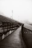 Running Track. A running track on early atmospheric morning fog with a view of grandstands Stock Image