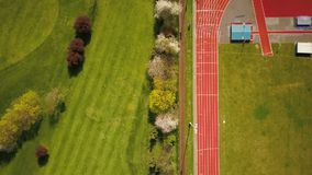 Running track; aerial drone view. Aerial drone view looking vertically down and following the lines of a running track flanked by green fields of the field area stock footage