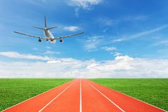 Running track with airplane landing and blue sky white cloud bac Royalty Free Stock Photos