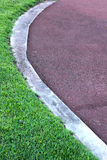 Running track - for  the athletes with green grass Stock Images