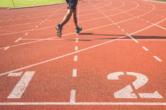 Running track for athletics. Running track with number and legs of runner Royalty Free Stock Photo