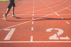 Running track for athletics. Running track with number and legs of runner Royalty Free Stock Images