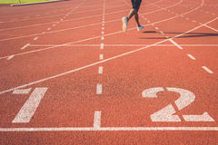 Running track for athletics. Running track with number and legs of runner Royalty Free Stock Photos