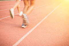 Running track with blur of runner feet in stadium Stock Photo