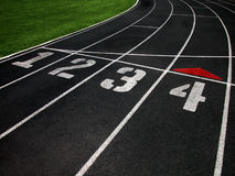 Running Track with Four Lanes. Shot of a black surfaced running track showing the lane markers of one through four and a grass covered infield Stock Image