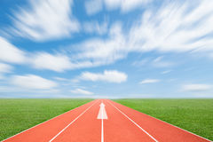 Running track with green grass and blue sky white cloud. Royalty Free Stock Photography