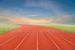 Running track with green grass and blue sky white cloud backgro Royalty Free Stock Images