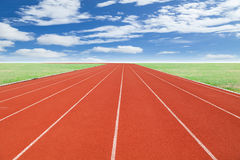 Running track with green grass and blue sky white cloud backgrou Stock Photos