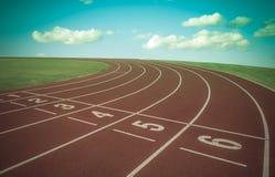 Running track between green grass in stadium. Stock Image