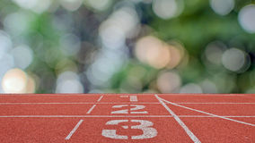 Running track number standard red color with bokeh. Stock Image
