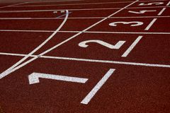 Running track with numbers, one to five, red surface with white lines royalty free stock photo