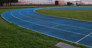 Running track outdoor in blue with white lines stock photography