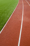 Running track rubber lanes in the artificial grass stadium. Stock Images