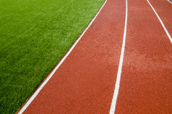 The running track rubber lanes in the artificial grass stadium Royalty Free Stock Photo