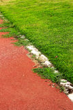 Running track for in the stadium - green grass. Royalty Free Stock Photo