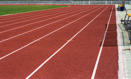 Running track in stadium. Racetrack, red rubber racetracks in big stadium evening Royalty Free Stock Image