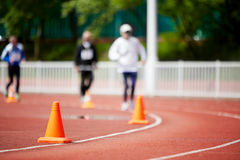 Running track at stadium with runners Stock Images
