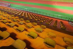Running track and stadium seats at night Stock Photos