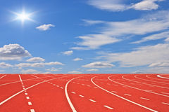 Running tracks and blue sky. With clouds and sun rays Royalty Free Stock Photography