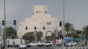 Running traffic in front of Museum of Islamic Arts in Doha, Qatar