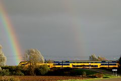 The running train and the rainbows. A running train is passing the level-crossing, while two rainbows are appearing. It is autumn Stock Images