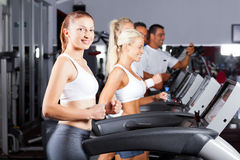 Running on treadmill. Fitness people running on treadmill in gym royalty free stock photography