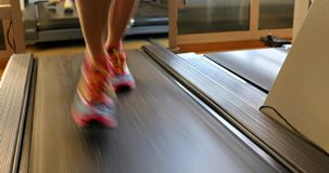 Running on treadmill. Fitness model woman running on treadmill with muscular legs indoor. Colorful gym shoes of girl on gym tapis roulant. Fast training indoor stock video footage