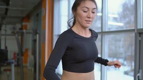 running treadmill Härlig idrotts- brunettkvinna i idrottshall lager videofilmer