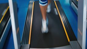 Running on treadmill. Women`s legs running on the treadmill stock footage