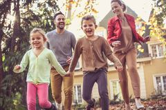 Running trough fall leaves is fun for all family. Smiling happy family royalty free stock image