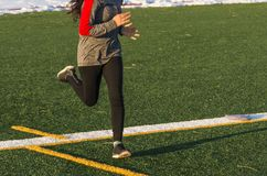 Running on a turf field with snow in the background. A high school female runner is running fast on a green turf field iin the winter, with snow lining the track Royalty Free Stock Image